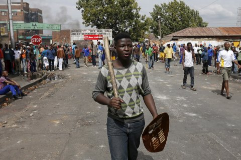 A man carries a club and a Zulu shield outside a hostel in Johannesburg(Siphiwe Sibeko:Reuters)