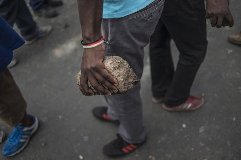 A man holds a brick near the hostels in the Jeppestown area of Johannesburg where clashes broke out(Mujahid Safodien:AFP)