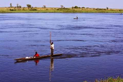 Here, a man paddles his wife and baby down the Zambezi River from, I assume, their village into the nearest town of Senanga.  In the background are two other canoes making a similar trip.
