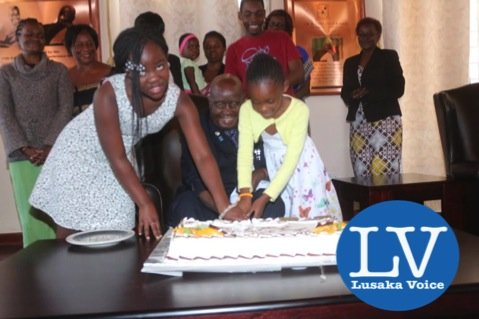 KK great grand daughters Gugu Letu Bwalya and Tiyezye Kaunda helping KK to cut a cake made for him. - Photo Credit Jean Mandela - Lusakavoice.com