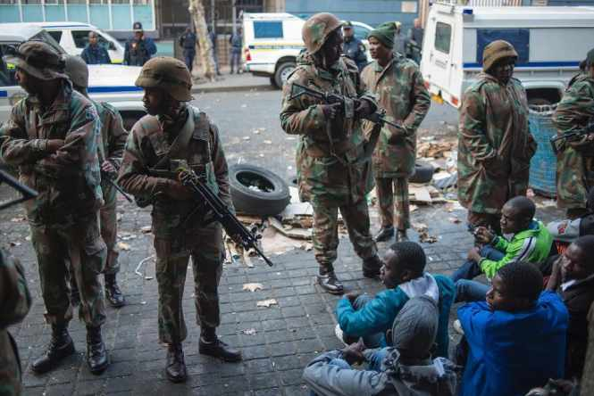 South African police and soldiers guard migrants after raiding buildings in Johannesburg's central business district on May 8, 2015 in an operation where over 300 illegal immigrants and foreign nationals were arrested (AFP Photo/Mujahid Safodien)