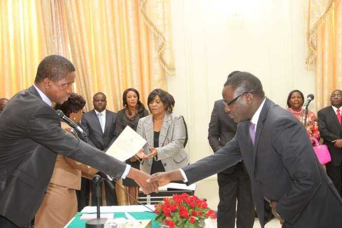 Zambia's Ambassador to France Humphrey Chibanda (r) being congratulated by President Edgar Lungu during the swearing -In-Ceremony at State House on May 4,2015 -Picture by THOMAS NSAMA