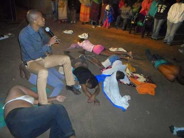 Pastor Penuel Mnguni makes congregation strip