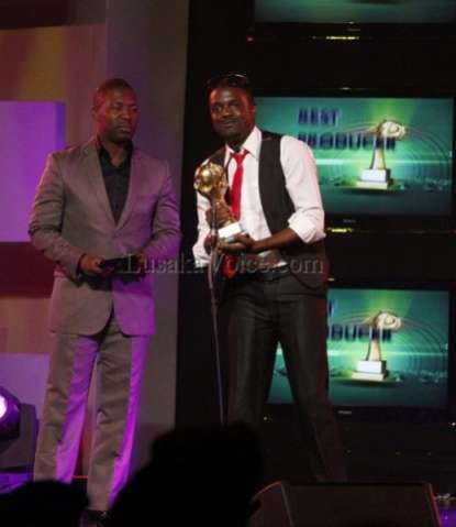 Former Zambian soap opera Kabanana actor Kangwa Chileshe presents the best producer award to Ben Blazer of the blazer studios