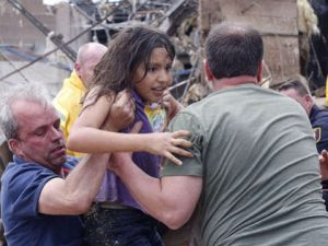 A child is pulled from the rubble of the Plaza Towers Elementary School in Moore, Okla