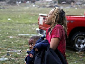 A woman carries an injured child to a triage center near the Plaza Towers Elementary School - AP
