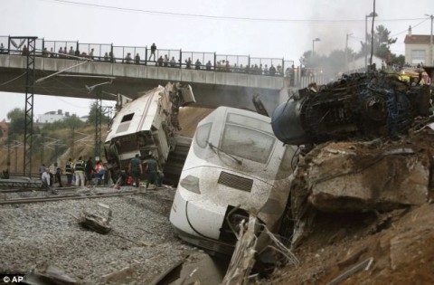 People look down from the rail bridge on the aftermath of a devastating train crash in north west Spain