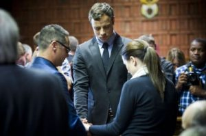 Oscar Pistorius icries as he prays with his sister Aimee and Brother Carl in the Magistrates court in Pretoria