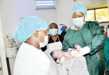 Taking charge of a life- First Lady Christine Kaseba (right) holds a baby after helping in the delivery at Choma General Hospital on Wednesday. – Picture by THOMAS NSAMA