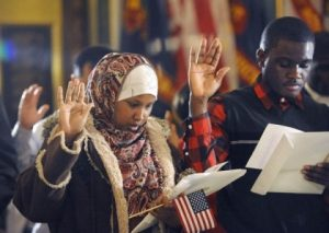 Nasra Isak, left, and Roy Maweja, right, are sworn in and naturalized as US citizens as 25 people from 18 different countries became official US citizens at the Capitol in Lansing Wednesday 12/4/2013. Isak, from East Lansing, is originally from Somalia, and Maweja, from Lansing, is originally from Congo.