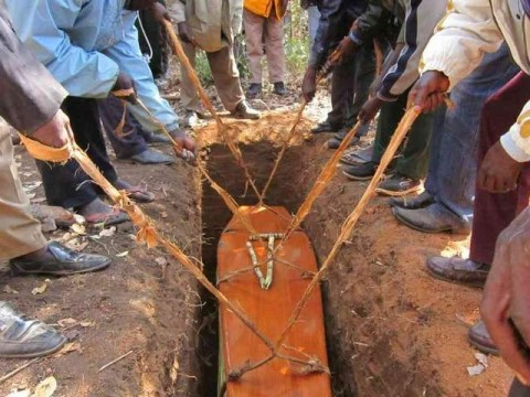 A coffin is lowered into the grave during a funeral in a Zambian village. At the end of the ceremony, the family members shovel soil back on top
