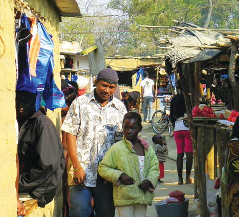 A father and his son beside their kiosk in the Manyama commercial market. The market has become a dense thicket of kiosks that continues to expand adjacent to the T5 Highway.