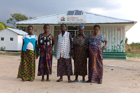 Doris Kangolo (far right) and her maternal grandmother Eunice (second from right) together with caregivers and other pregnant women outside the Fiwale Maternity Waiting House. (@ UNICEF:Christine Nesbitt)
