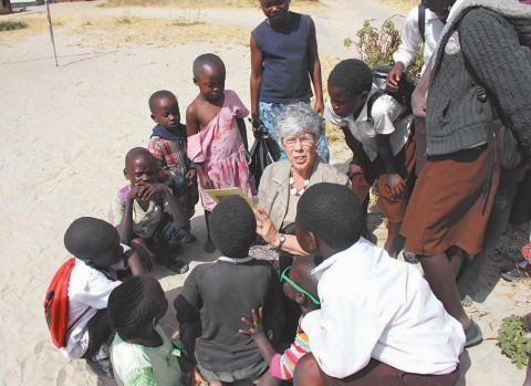 JOANNE BOLLINGER, of Brunswick and resident of Thornton Oaks retirement community, reads to children from the Sishekanu Basic School on her trip last June to Zambia. CONTRIBUTED PHOTO