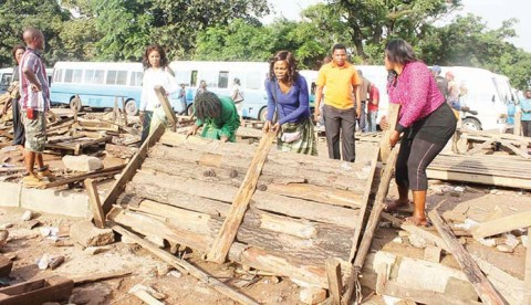KITWE City Council community Police on Thursday removed all wooden stalls mounted on curbs and sidewalks in some parts of the city centre. These vendors were captured picking up debris of their broken stands. – Picture by NKOMBO KACHEMBA.