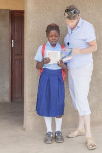 Project Luangwa charity manager Karen Beattie helps a local student with her schoolwork. (Photograph by Marcus and Kate Westberg)