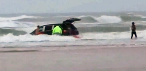 In this image made from video and released by Simon Besner, lifeguards rescue children from a minivan that their mother drove into the Atlantic Ocean, Tuesday, March 4, 2014 in Daytona Beach, Fla.