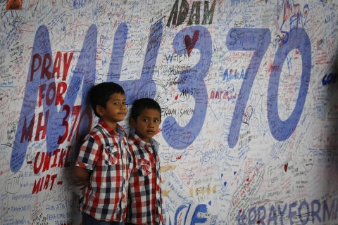 Two Malaysian children stand in front of messages board and well wishes to people involved with the missing Malaysia Airlines jetliner MH370, Sunday, March 16, 2014
