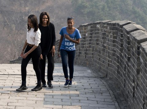 This March 23, 2014 file photo shows first lady Michelle Obama walking with her daughters Malia, left, and Sasha, right, as they visit the Mutianyu section of the Great Wall of China in Beijing.