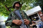 A Thai army soldier stands guard outside the National Broadcasting Services of Thailand