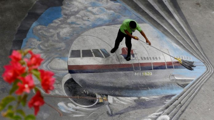 A school utility worker mops a mural depicting the missing Malaysia Airlines Flight 370 Tuesday,