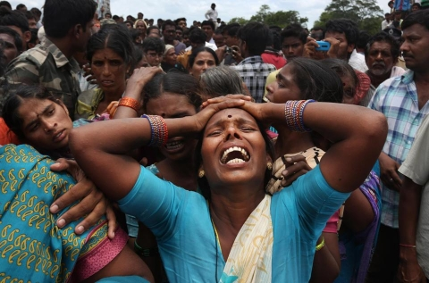 A relative of a victim cries at the site of a train that crashed into a school bus in Medak district in the southern Indian state of Telengana, Thursday, July 24, 2014. Twelve children were killed Thursday (AP Photo:Mahesh Kumar A.)