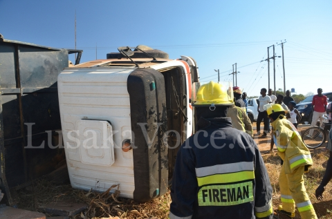 Firefighters inspect the overturned truck