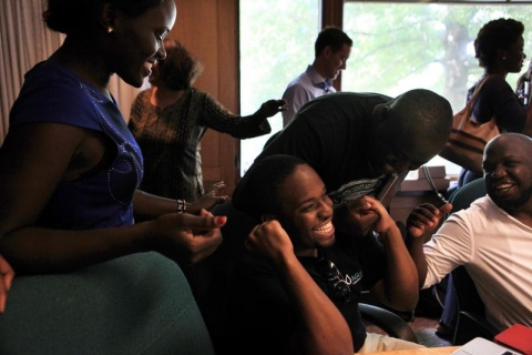 as Lydia Munika, of Kenya, left, Bruce Ernest, of Zambia, second from right, and Tumiso Mabusela, of Botswana, right, congratulate Mshila Sio, of Kenya, middle, after he learned that he received a grant during the last week of the Young African Leaders Initiative at Dartmouth College in Hanover, N.H. on July 23, 2014. (Valley News - Ariana van den Akker)