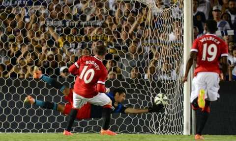 Manchester United's Wayne Rooney scores from the penalty spot as LA Galaxy goalkeeper Brian Perak attempts a save during their in Pasadena, California on July 23, 2014 (AFP Photo/Frederic J Brown)