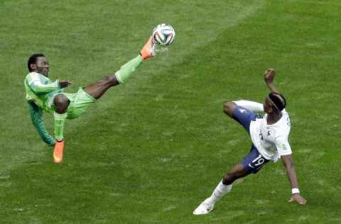 Nigeria's Juwon Oshaniwa, left, and France's Paul Pogba challenge for the ball during the World Cup round of 16 soccer match between France and Nigeria