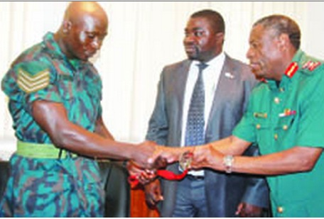 JUDOKA Boas Munyonga (left) presents the bronze medal he won at the 2014 Commonwealth Games in Scotland to Zambia National Service (ZNS) commandant, Nathan Mulenga in Lusaka yesterday as Zambia Judo Association president Alfred Foloko looks on. Picture courtesy of ZNS