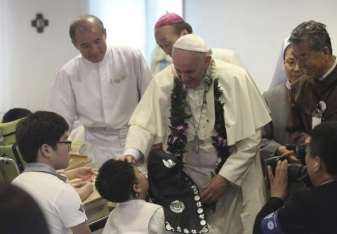 Pope Francis blesses a disabled child during his visit to the rehabilitation center for disabled people at Kkottongnae in Eumseong, August 16, 2014.