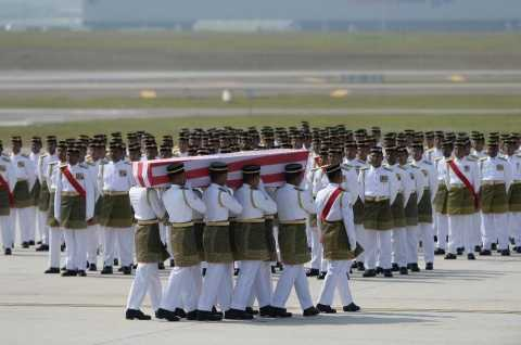 Soldiers carry a coffin with the remains of a Malaysian victim from Flight MH17 during a ceremony at Kuala Lumpur International Airport in Sepang on August 22, 2014 (AFP Photo/Manan Vatsyayana)