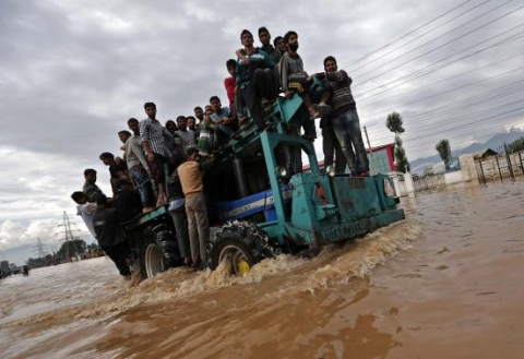 A tractor evacuating Kashmiri flood victims to higher grounds travels through a flooded street in Srinagar September 9, 2014.