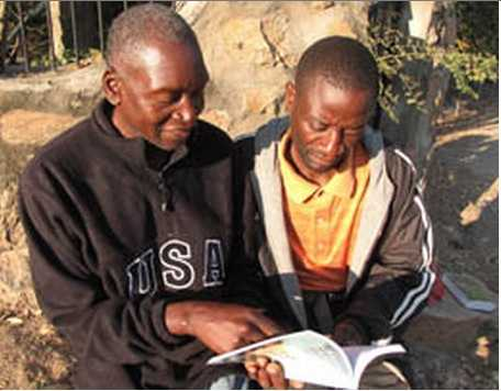 MB photo by James Langston Passmore Hacaba, who has endured persecution for his faith, discusses a Bible verse with Tonga believer Maxwell Mwaanga.