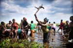 A woman kills a water monitor lizard while clearing weeds with machetes on the Barotse flood plain, Zambia, on 18 November 2012
