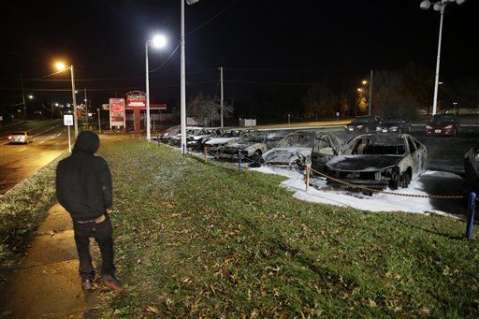 A pedestrian passes by damaged cars in a used car dealership Tuesday, Nov. 25, 2014, in Dellwood, Mo.