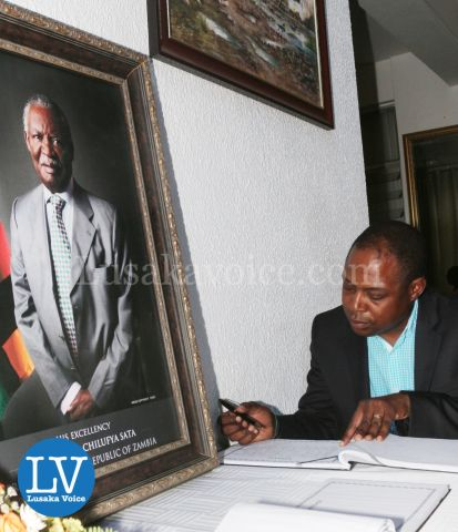 FAZ President Kalusha Bwalya; FAZ spokesperson Nkweto Tembwe sign book for Sata