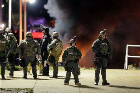 Police arrive at a business Tuesday, Nov. 25, 2014, in Dellwood, Mo., as cars in a parking lot next to the building burn.