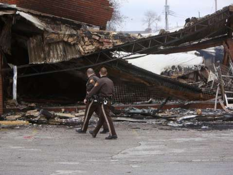Police officers walk past the smoldering remains of a beauty supply store at the corner of Chambers Road and West Florissant Avenue, Nov. 25, 2014, in Ferguson, Mo.