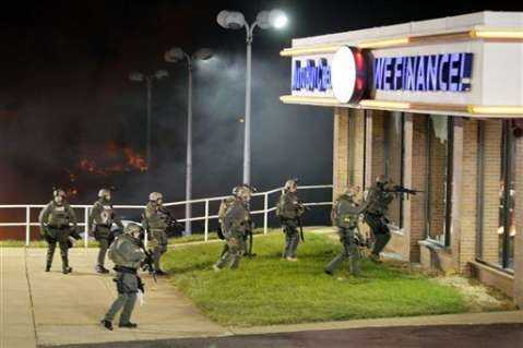 Police arrive at a business Tuesday, Nov. 25, 2014, in Dellwood, Mo., as cars in a parking lot next to the building burn