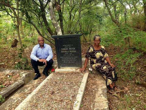 Nevers Mumba at his father's grave with his older sister Mrs Mulenga