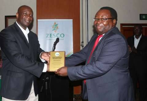 """ZESCO Managing Director Cypriano Chitundu shaking hands with Zambia Environment Management Director General Joseph  Sakala as he receives a ZEMA award in recognition of """"Consistency to Environmental Impact Assessment Regulations""""'; the ceremony took place at the Lusaka Southern Sun Ridgeway Hotel on Tuesday evening, December 23rd, 2014."""