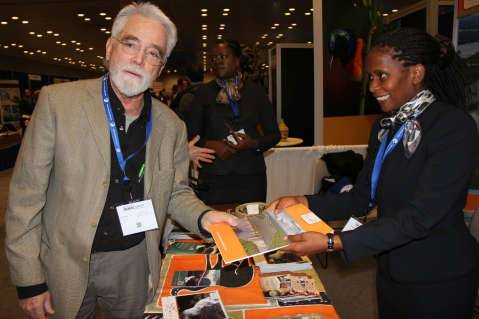 5. Ministry of Tourism acting principal tourism development and research officer Chilala Habasimbi giving a brochure to a visitor at the Zambian stand during the New York Travel Show on Friday 23 January, 2015