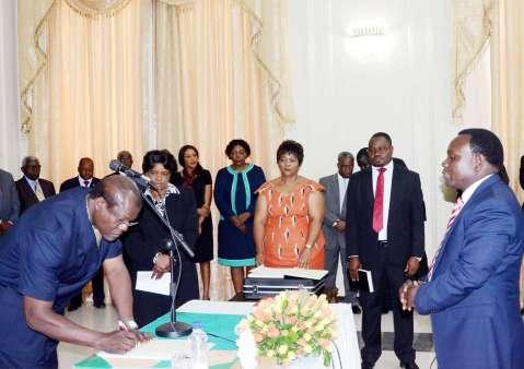Acting President Ngosa Simbyakula signs on the affidavit of Oath of Muchinga province permanent Secretary Bright Nundwe (r) during the Swearing-In-Ceremony at State House on March 13,2015 -Picture by THOMAS NSAMA