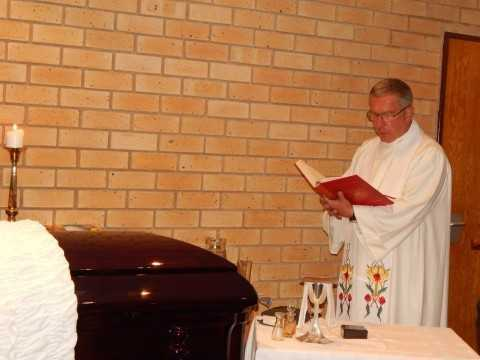 Father James Ralston blessing late Mr. Willie Nsanda's coffin - Photo Credit Nicky Shabolyo