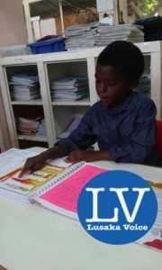 Kaunda Emmanuel Chikota takes his grandparents through his portfolio which was packed with activities and all materials of what he had been studying on a daily basis. - Lusakavoice.com