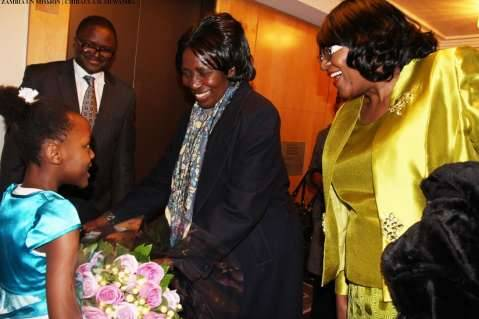 Zambia Vice-President Her Honour Mrs Inonge Wina (second right) receives a bouquet of flowers from eight-year-old Tasheni Bota on arrival at New York Palace Hotel in New York on Sunday, March 8, 2015. Looking on is Zambia's Ambassador to the UN Her Excellency Dr Mwaba Kasese-Bota (right) and Zambia's Ambassador to the US His Excellency Mr. Palan Mulonda. The Vice-President is leading the Zambian delegation to the 59th Session of the Commission on the Status of Women. PHOTO   CHIBAULA D. SILWAMBA   ZAMBIA UN MISSION