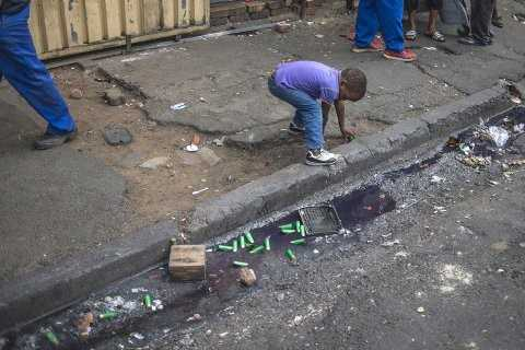 A child picks up casings from the rubber bullets fired by police in Jeppestown, Johannesburg(Mujahid Safodien:AFP)