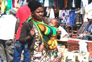 A mother carrying a baby in front using a chitenje cloth in Lusaka. It is easier to breast feed the baby if needed.